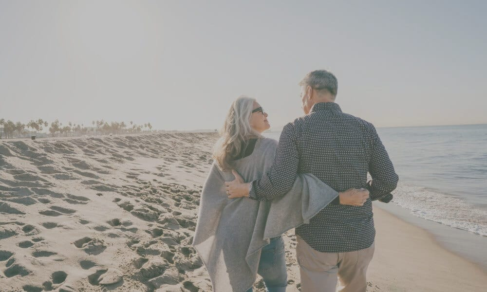 retired couple walking on the beach with arms wrapped around each other