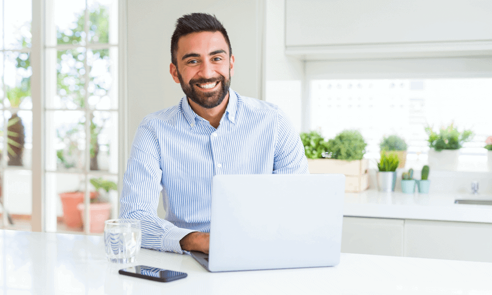 man looking at camera at home with computer in front of him
