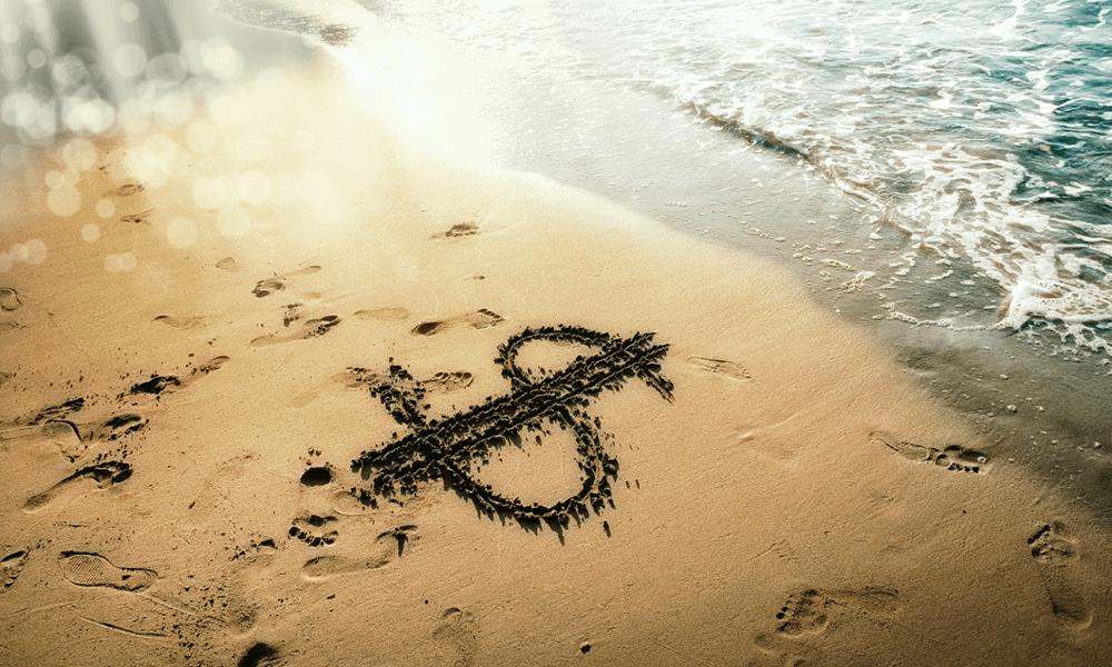 money sign written in sand at beach
