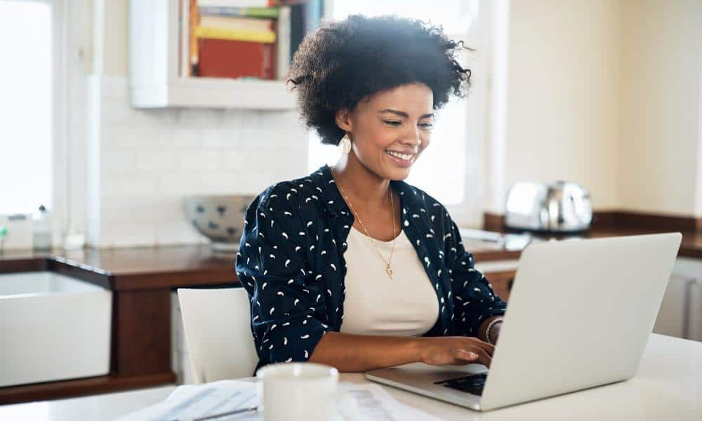 Women working at home on computer in kitchen
