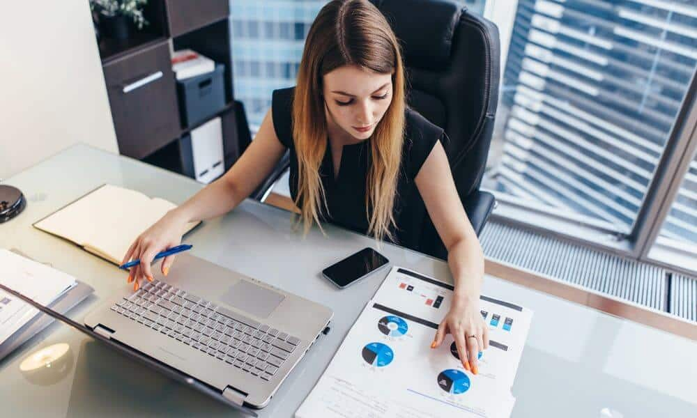 Professional business women working with computer and papers at desk