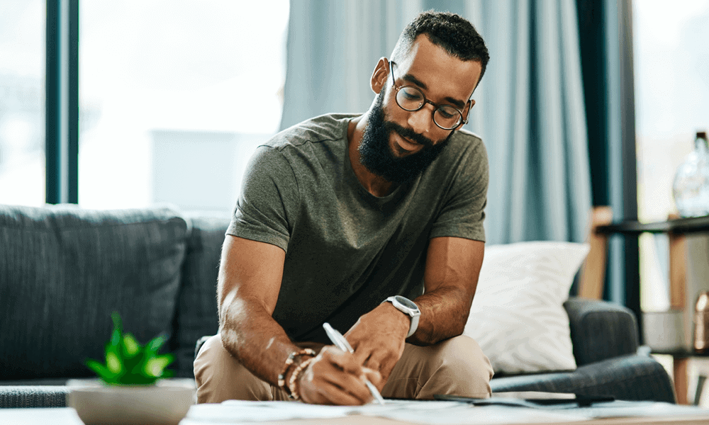 Man sitting on couch writing on papers