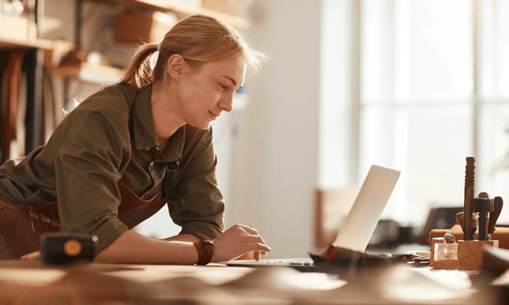 Woman leaning on table working on computer