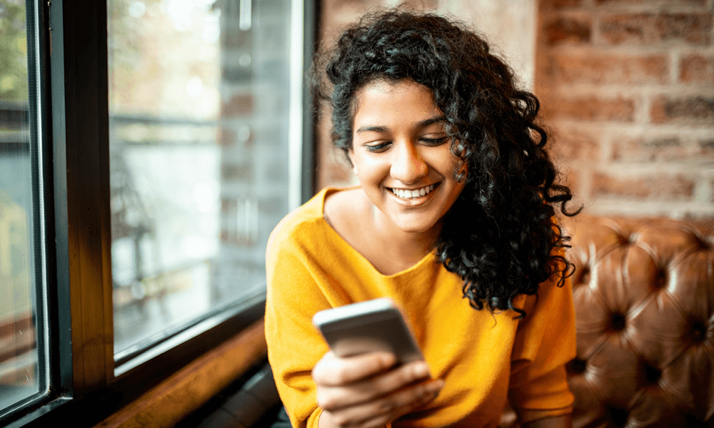 Women smiling while on phone sitting on couch