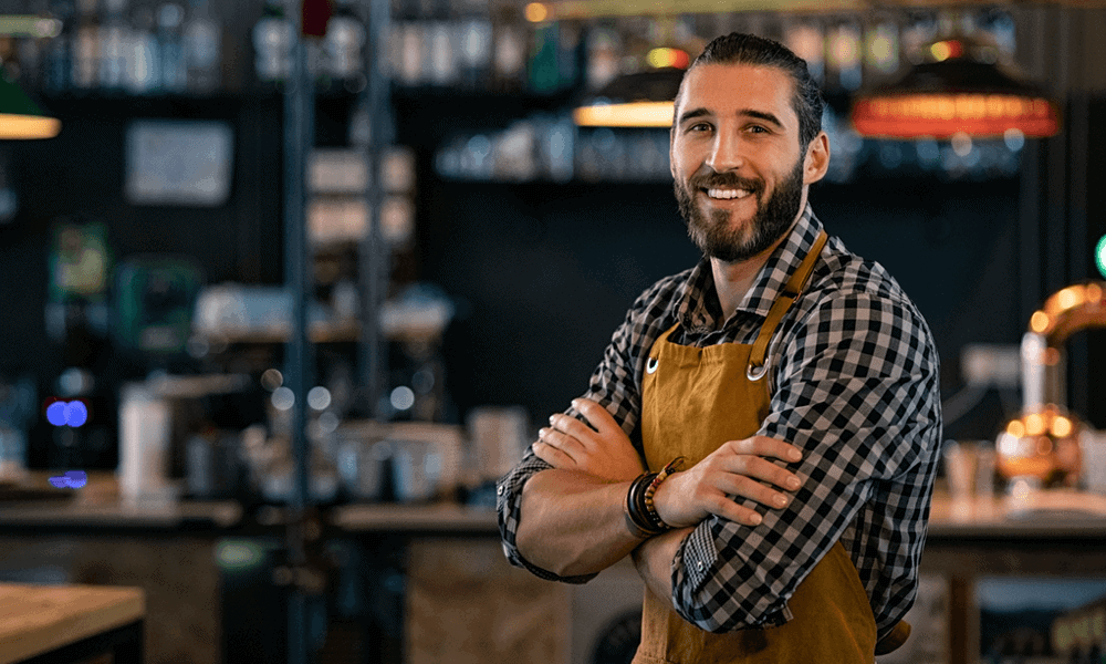 Man standing in restaurant with arms cross smiling at camera