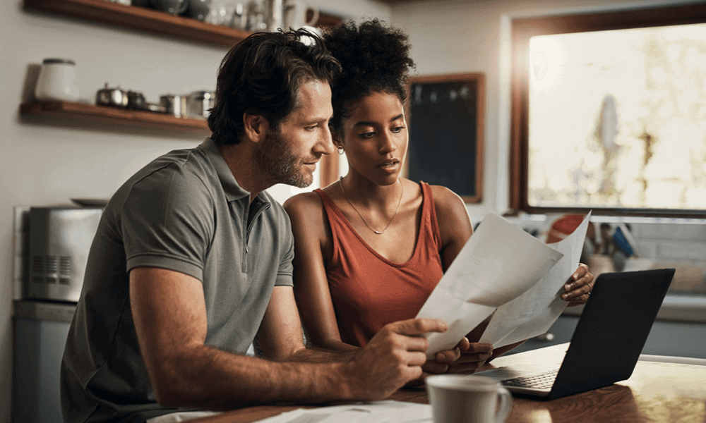 Couple looking over papers while working on computer at home