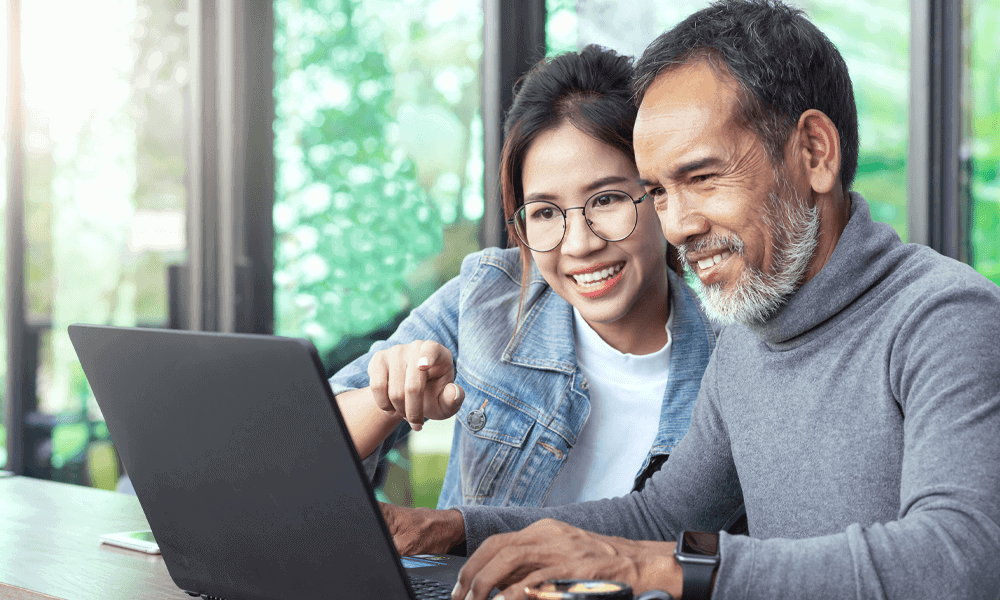 Father and daughter smiling while working on computer