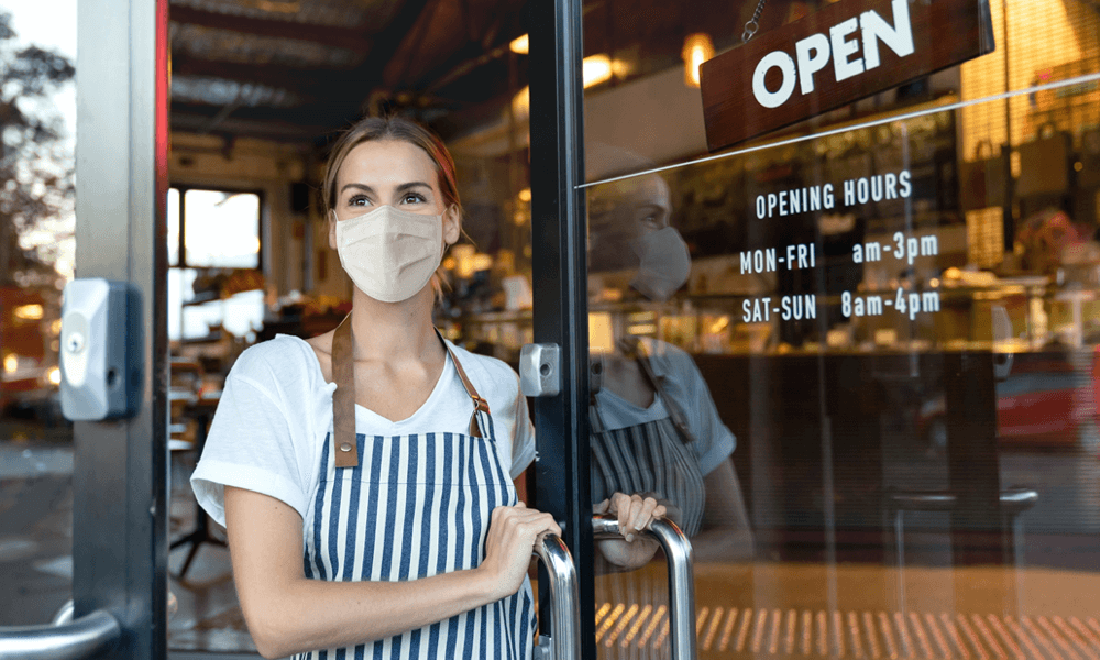 Business owner standing in door looking in distance with mask on