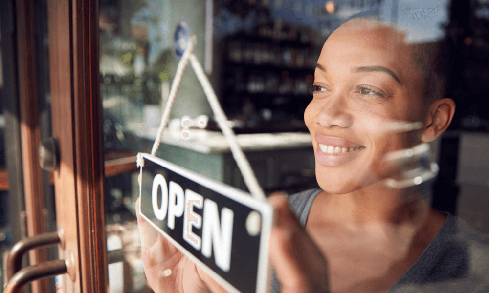 "Woman looking out window with business sign ""open"" in front of her"