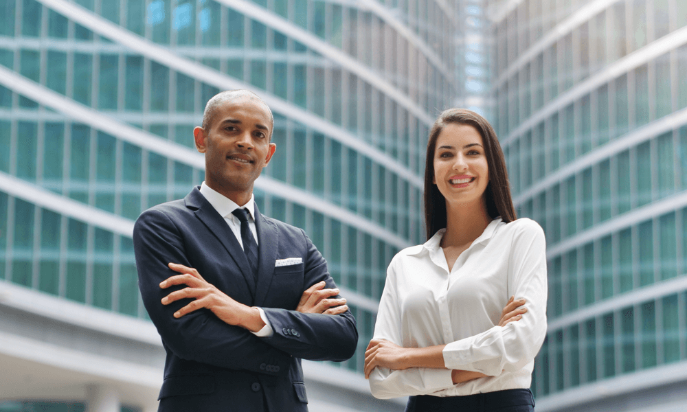Two business professionals crossing arms looking at camera