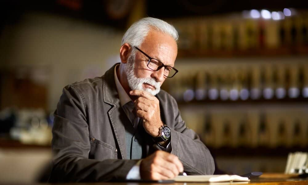 Older man sitting down looking at book holding chin while thinking