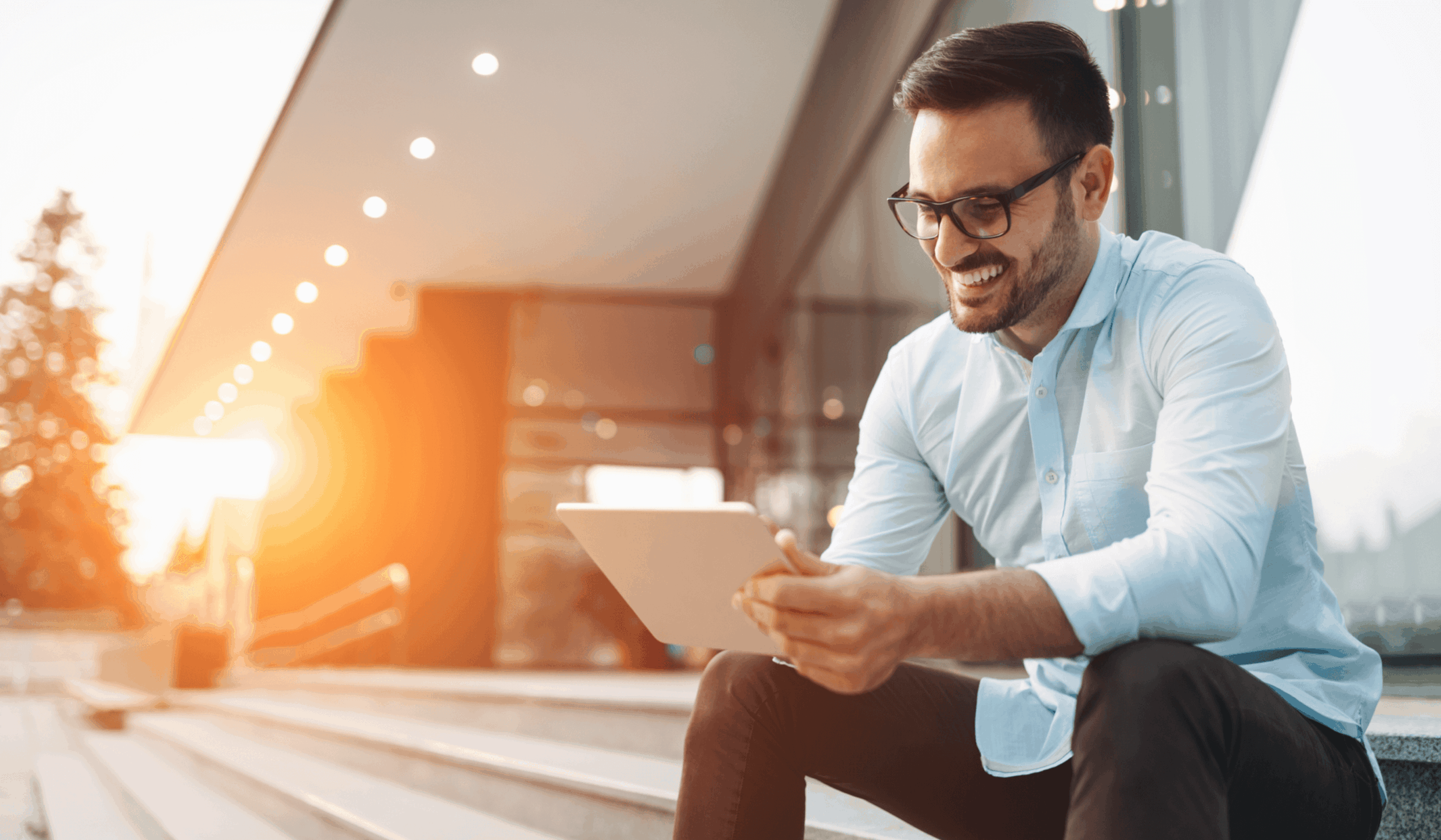 Business man sitting on stairs outside on tablet smiling at sunset